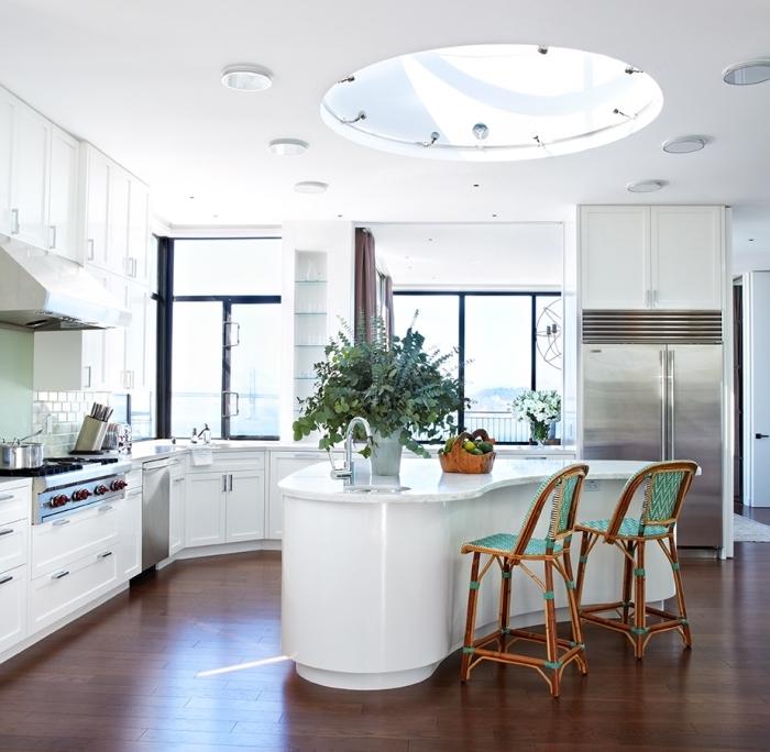 cuisine blanche moderne avec des électroménagers en acier inoxydable et un ilot centrale ergonomique d'une forme arrondie
