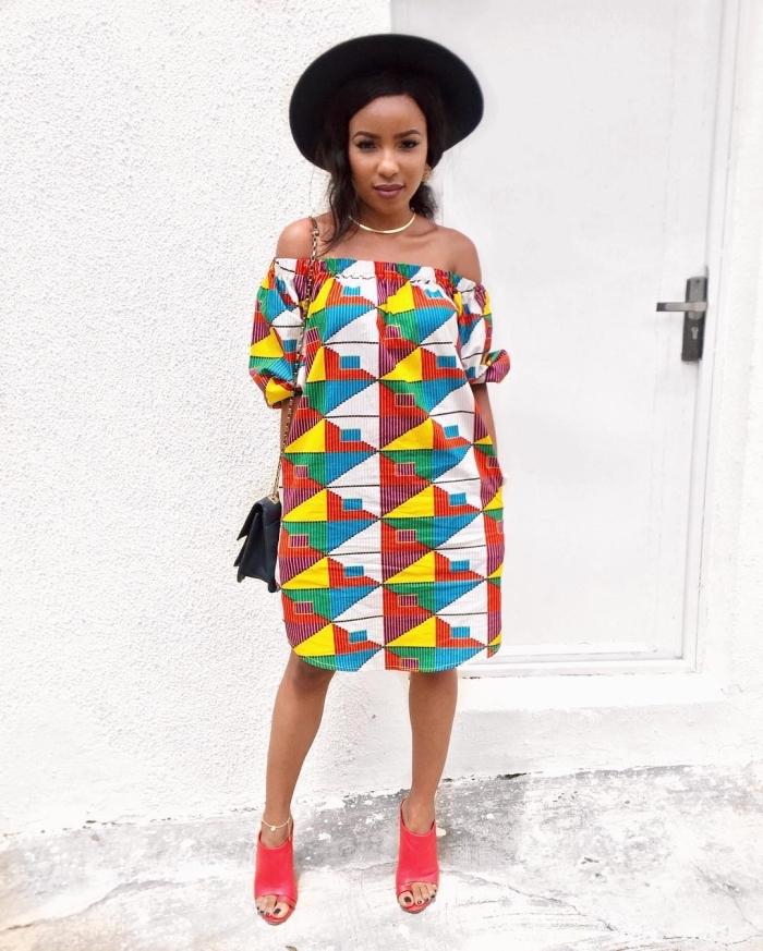 tenue africaine moderne facile à accessoiriser, robe tunique à épaules dénudées et bustier élastique portée de façon chic avec un chapeau noir à large rebord