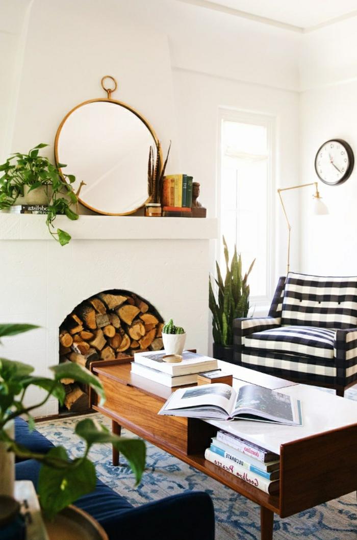 miroir rond et plantes vertes autour d'une cheminée blanche décorative, fauteuil rayé, tapis floral