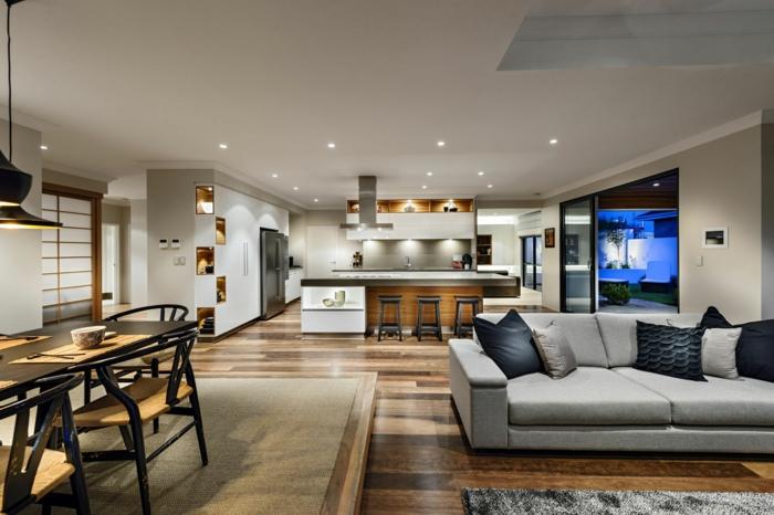 cuisine semi ouverte sur salon, tabourets noirs, sofa gris, sol en bois, table de repas élégante, déco gris et bois