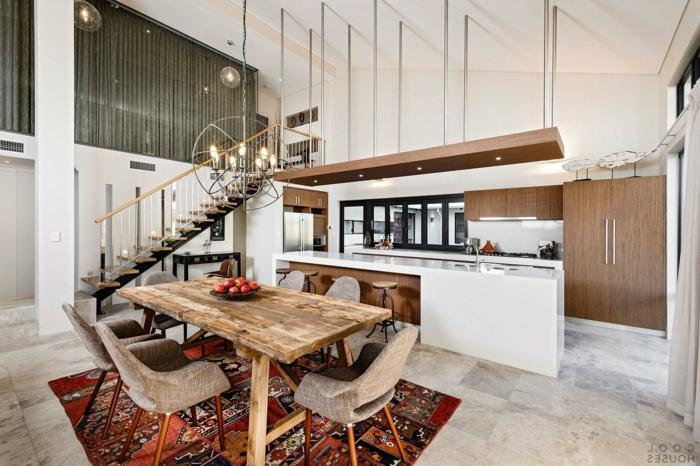 separation cuisine salon avec grand comptoir blanc, tapis patchwork style ethnique, table en bois brut, escalier loft