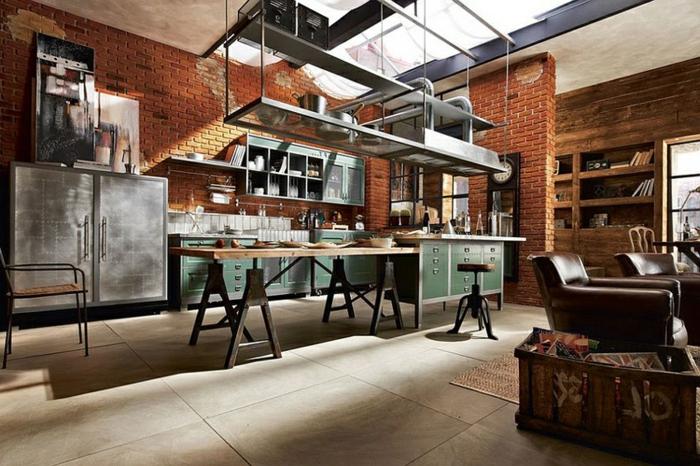 cuisine semi ouverte sur salon, grande table en bois et fer, dol en grands carreaux gris, mur en briques, placards et armoire de cuisine en métal