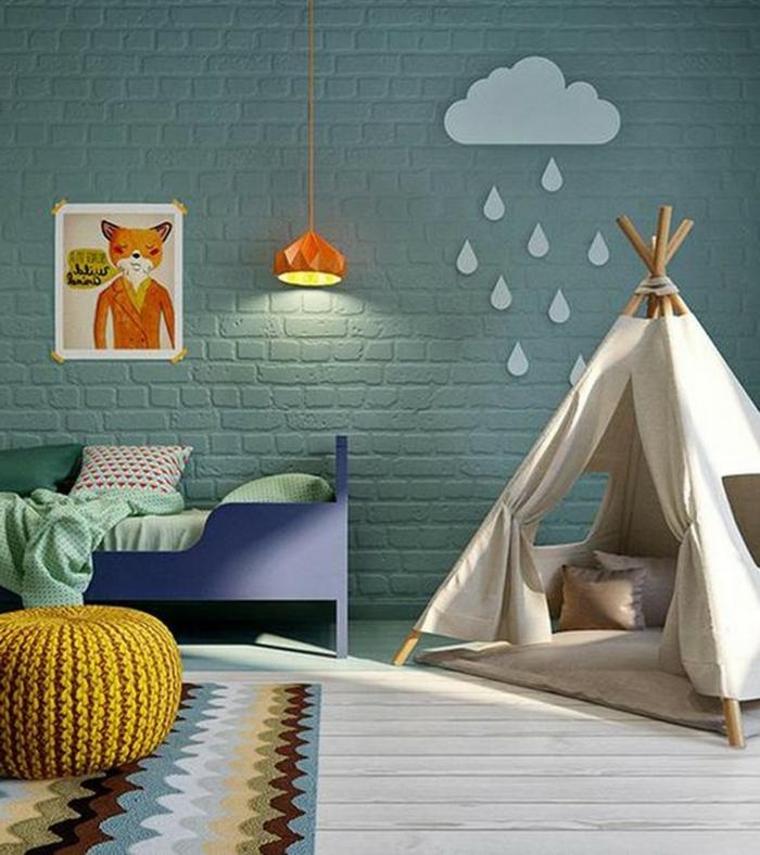 mur en briques vertes, tipi enfant, tabouret jaune tricoté, lit enfant bleu, dessin encadré et lampe orange