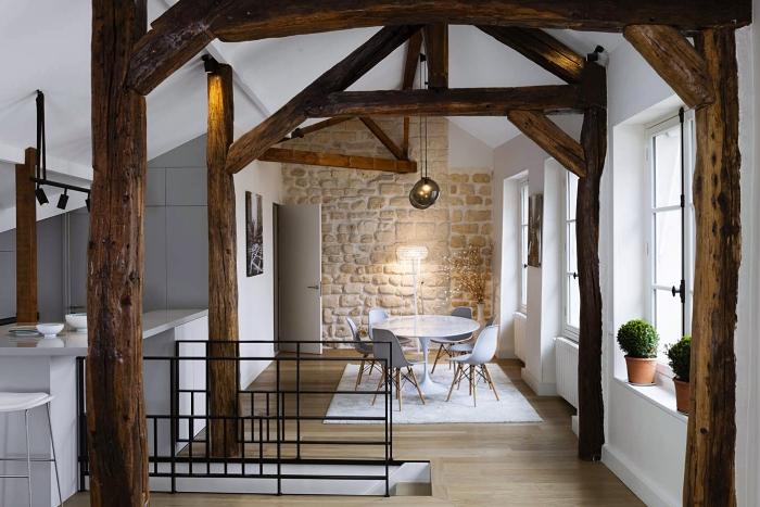 design intérieur moderne et traditionnel dans un petit studio avec revêtement mural en pierre et charpente de bois brut apparente