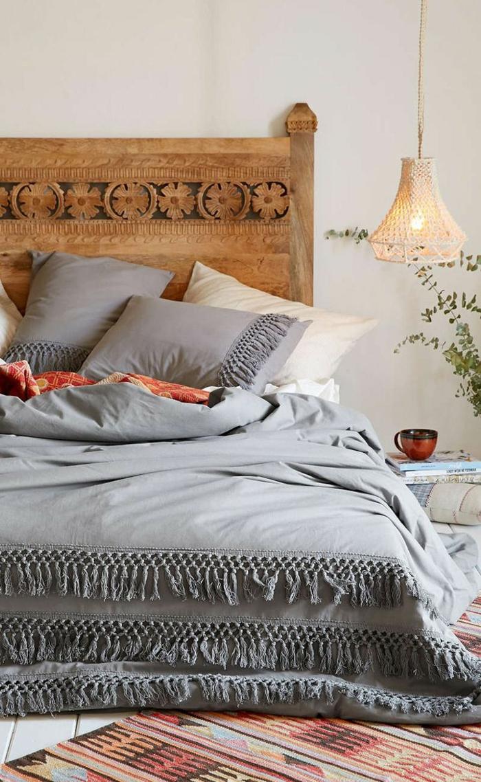 chambre bohème, tête de lit bois, lampe pendante, parure de lit grise, coussins gris, carpette ethnique