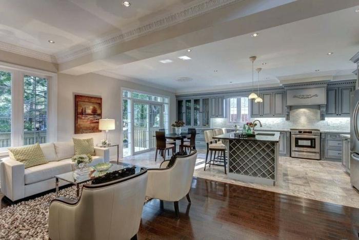 separation cuisine salon esthétique, sol en bois, chaises blanches, tapis moelleux beige, peinture blanche, ilot de cuisine haut avec des chaises