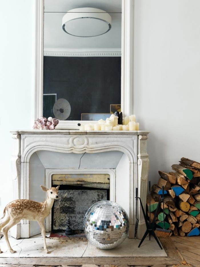 cheminée blanche, bougies blanches, boule disco, biche, bûches aux extrémités peintes