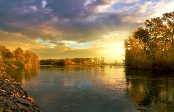 jolie paysage d'automne, rivière aux eaux calmes, nuages orageux, forêt