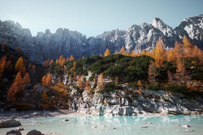 lac bleu sous une colline rocheuse, pins et sommets rocheux, paysage pour fond d'écran