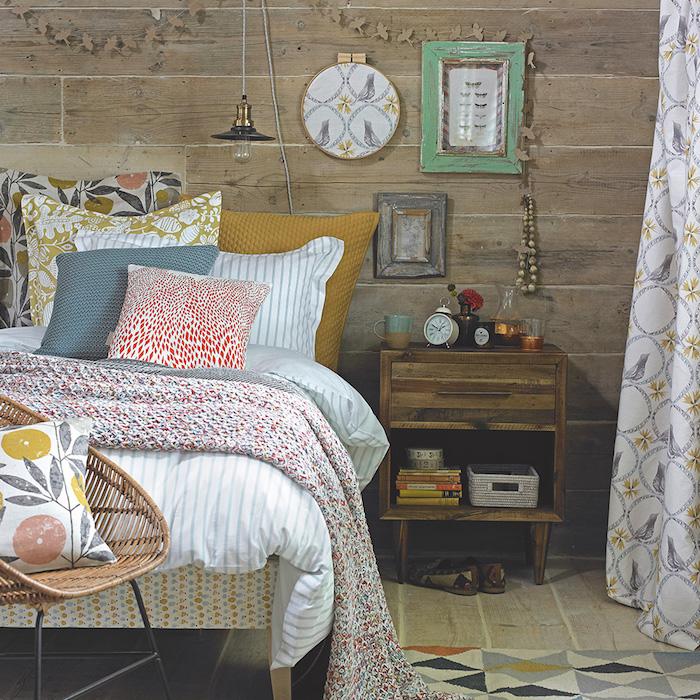 murs et sol en bois, linge de lit et coussins à motifs fleuris, table de nuit en bois brut décorée d objets vintage, chaise en rotin