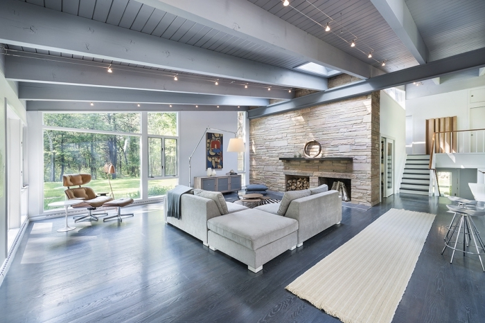 exemple design intérieur moderne dans un salon spacieux avec cheminée en pierre et larges fenêtres, idée comment peindre des poutres en blanc cérusé