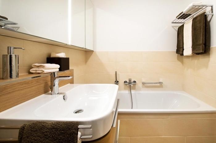 quelles couleurs pour une petite salle de bain claire, modèle de petite baignoire intégrée dans une salle de bain au carrelage beige