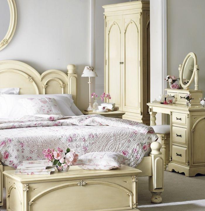coiffeuse, armoire, bout de lit et lit blanc cassé patinés, linge d elit fleuri, deco shabby chambre à coucher, tapis gris, murs blancs