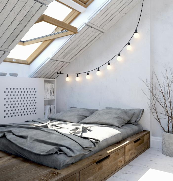 lit en bois bas, sol en planches peintes blanches, guirlande d'ampoules, fenêtre en pente, décoration chambre adulte moderne