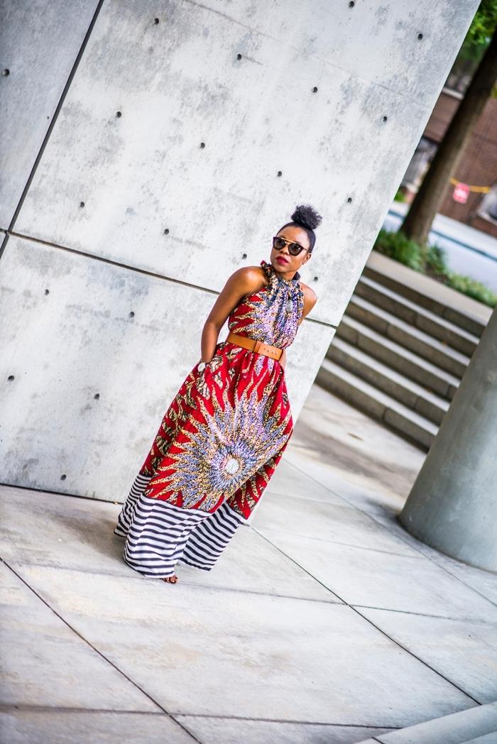 tenue africaine pour la femme moderne, robe longue et fluide à motif africain gros soleil, avec des rayures sur le bas portée avec ceinture à la taille