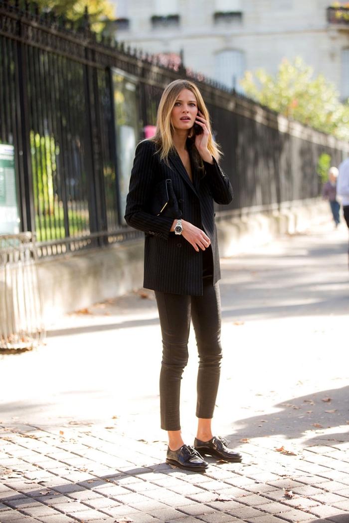 modèle de chaussures plates femme, vision élégante en pantalon slim et blazer noir avec chaussures derbies noirs