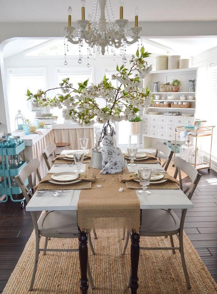vaisselier blanc vintage, table en bois avec plateau blanc et chaises en bois usés, tapis beige, lustre élégant, sol parquet marron, deco maison de campagne