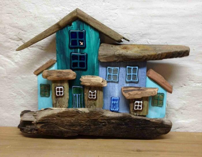 maison peinte bleue avec bois flotté, plusieurs toitures an bois flotté