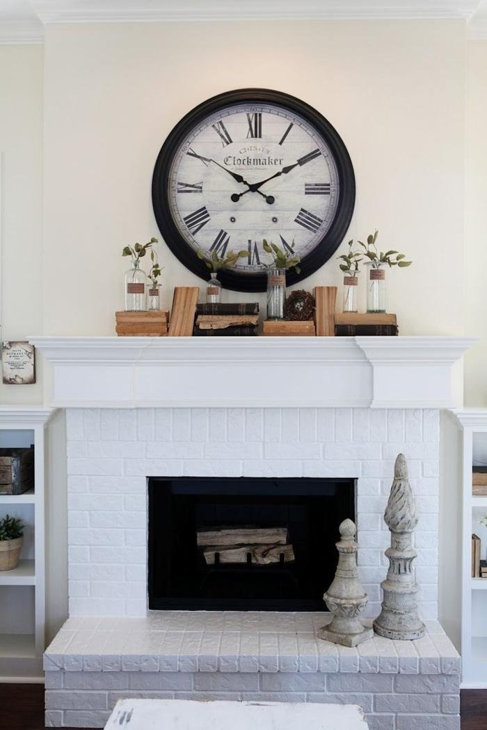 foyer décoratif blanc, horloge style shabby et vieux livres sur une cheminée blanche décorative