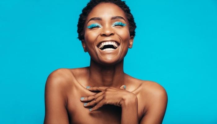 coupe courte frisée, exemple comment styliser les cheveux crépus courts, modèle de maquillage flashy aux fards à paupières bleu électrique