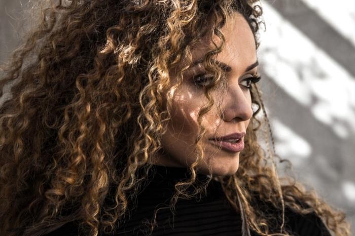 coloration tendance aux mèches dorés sur cheveux de base châtain foncé, coiffure blow out sur cheveux frisés