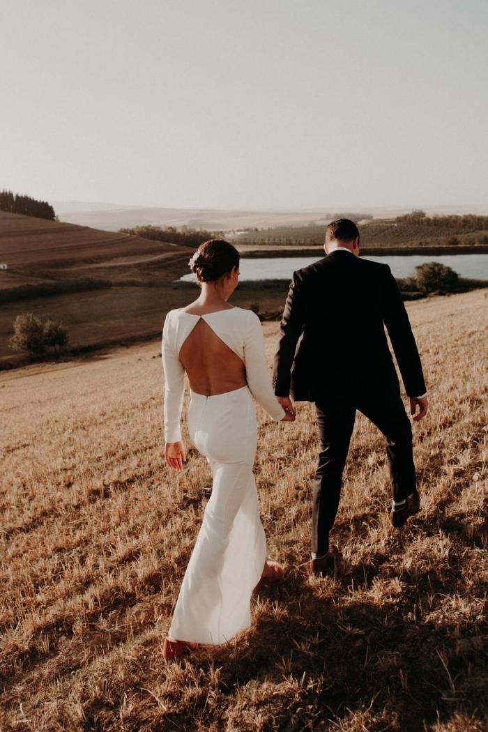 le dos décolleté d'aspect géométrique de cette robe de mariée manche longue joue l'effet de contraste avec la simplicité de sa coupe