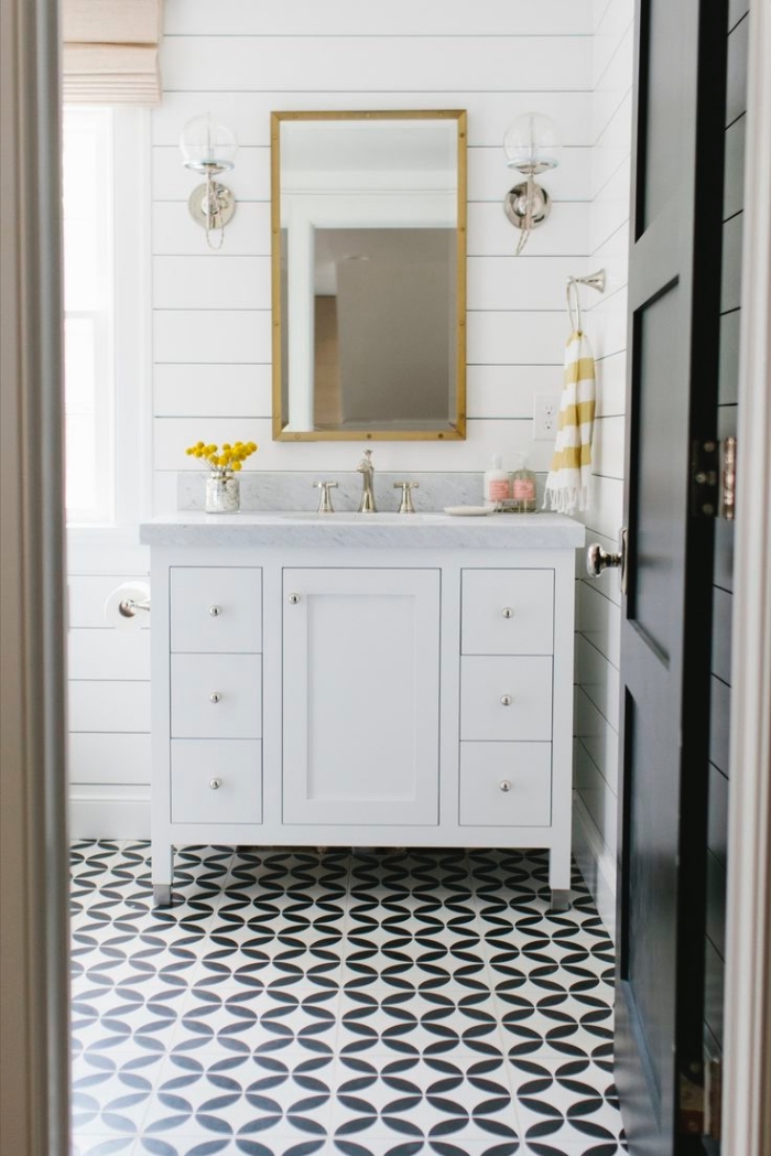 utilisez les carreaux de ciment noir et blanc au sol pour créer un joli effet graphique dans une salle de bains monochrome