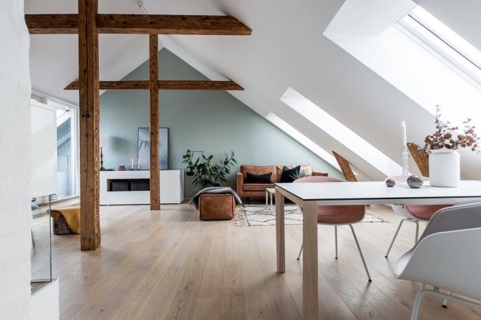esprit minimaliste dans une pièce mansardée aux murs blancs avec charpente apparente de bois massif foncé