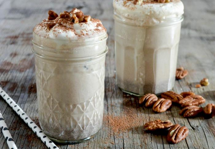deux pots de milkshake aux pecans, pailles pointillées, planches de bois, noix de pécan