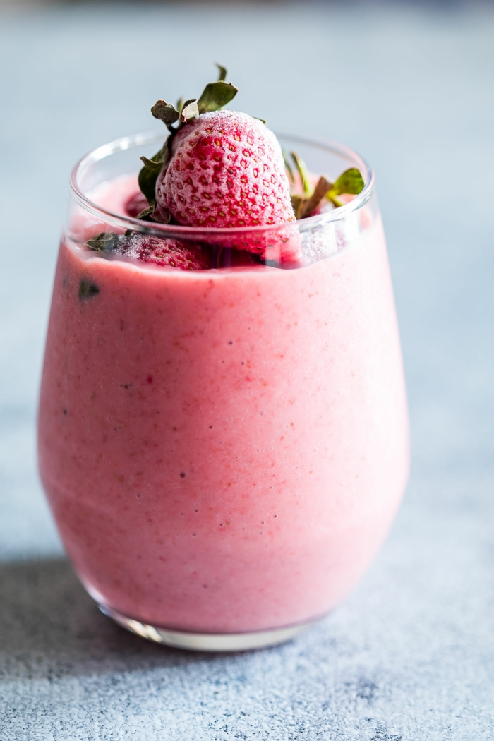 milkshake lait et fraises congelées, topping fraises, petit verre plein d'un liquide crémeux et rose