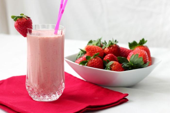 assiette blanche pleine de fraises, serviette rouge, tasse de milkshake aux fraises classique