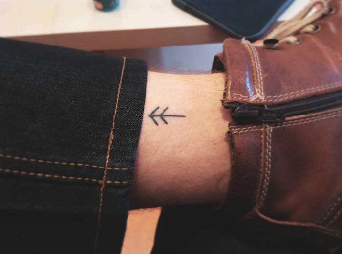 mini tatouage minimaliste et discret sur intérieur de la cheville avec petite flèche