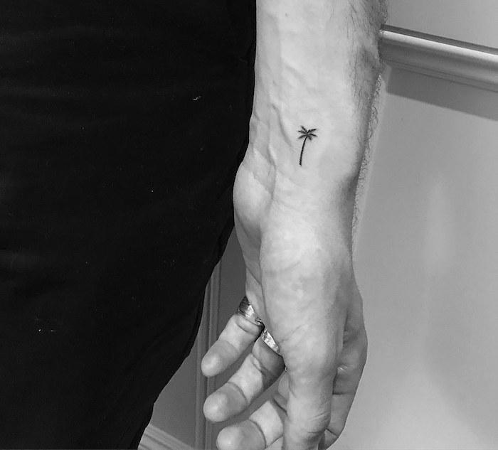 photo de mini tatouage discret palmier noir sur le poignet homme