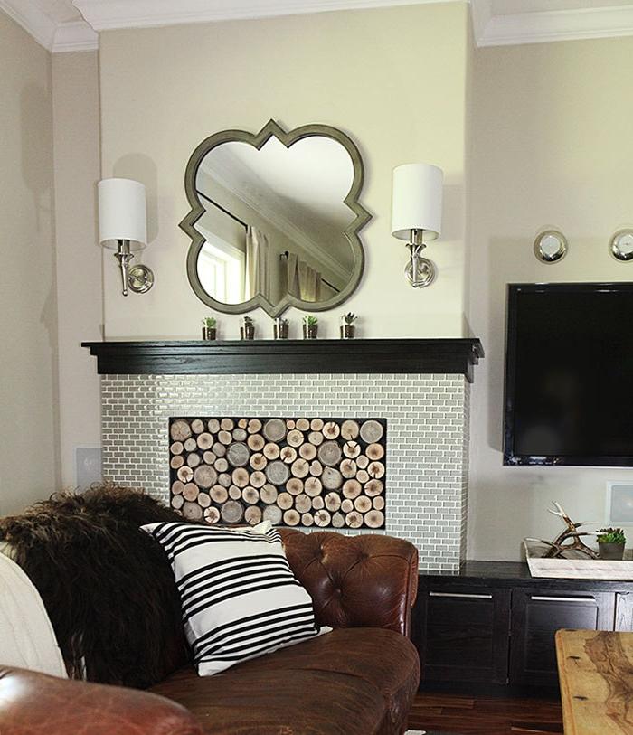 miroir décoratif, grande cheminée murale, fauteuil en cuir confortable, salon contemporain à déco cosy