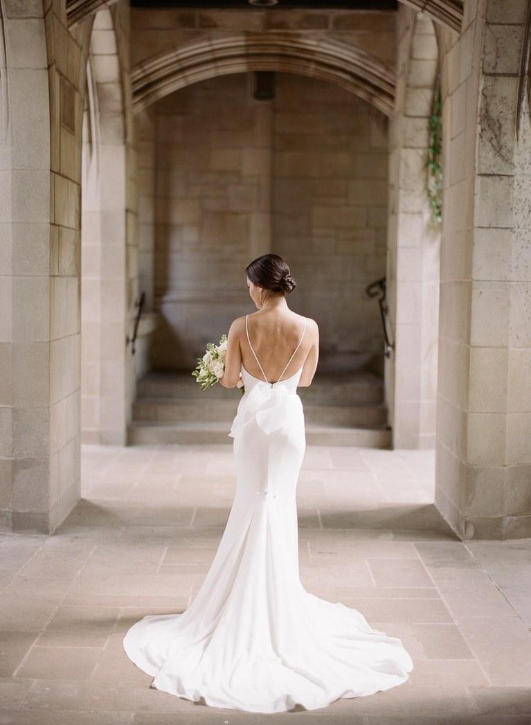 robe de mariée fourreau élégante et féminine avec un décolleté dos mis en valeur par deux fines bretelles et un noeud romantique à la taille
