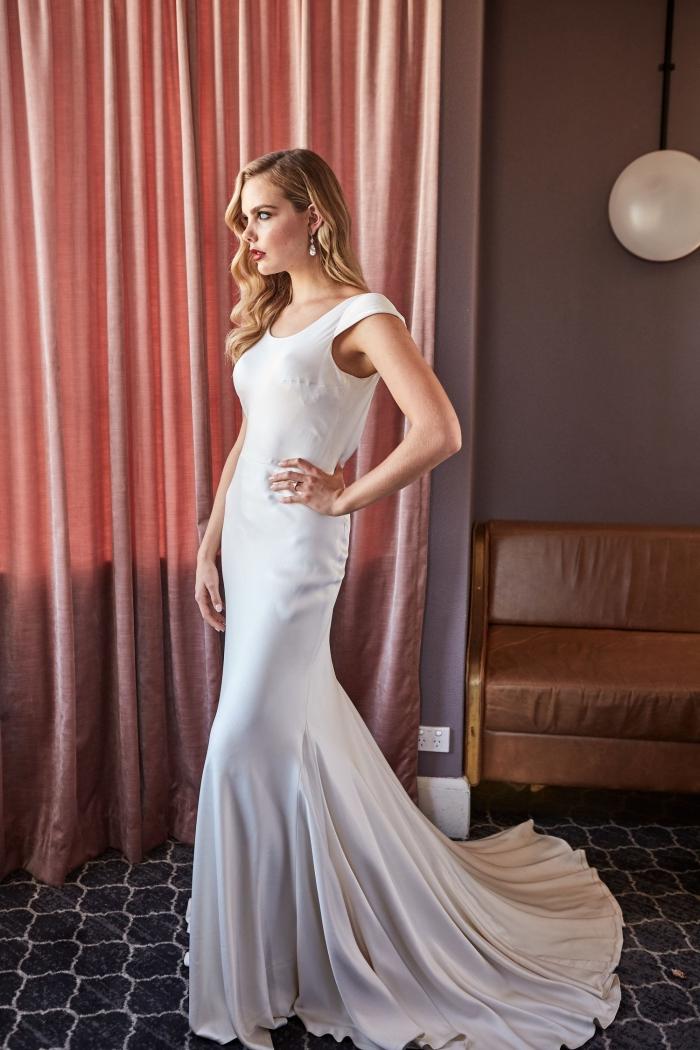 la simplicité de cette robe de mariée sirène à tombé parfait est contrebalancée par un décolleté dos sensuel