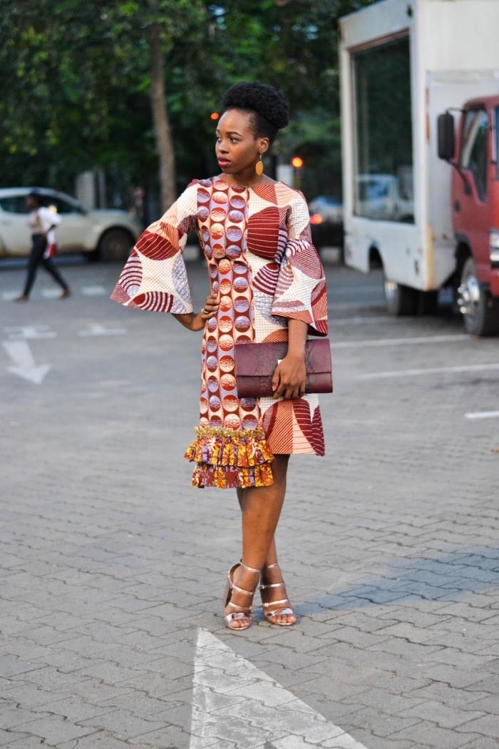 modèle de robe africaine moderne et chic avec manches trois-quart évasées, à motifs tribaux dans les tons ocre accessoirisée avec une pochette en cuir bordeaux
