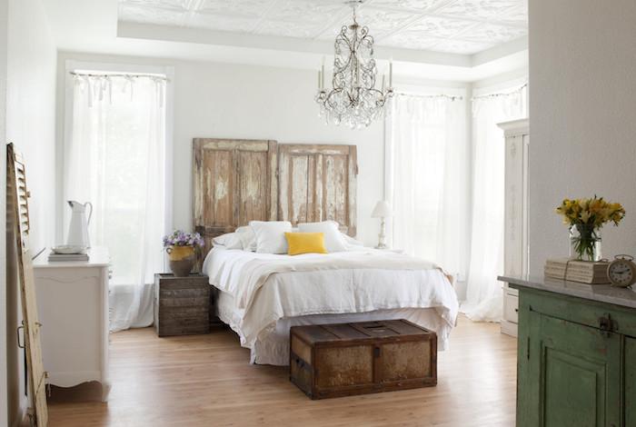 campagne decoration vintage avec tete de lit en portes bois granges, coffre vintage en guise de bout de lit, table de nuit bois brut, linge de lit blanc, parquet clair, lustre baroque
