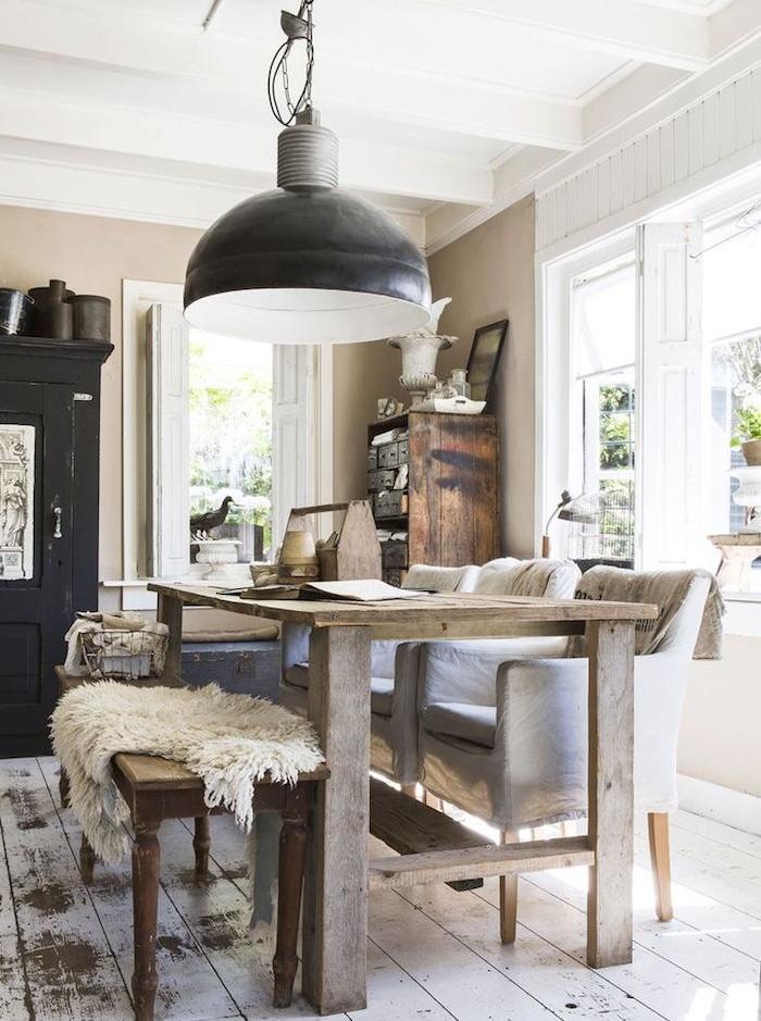 table salle à manger bois brut, bacn bois et fauteuils en tissu gris, parquet patiné, suspension style campagne, mur couleur taupe, vaisselier bois brut