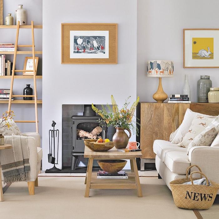 table basse bois clair, canapé et fauteuil gris clair, panier de rangement, murs couleur gris clair, étagères bois ouvertes, cheminée noire