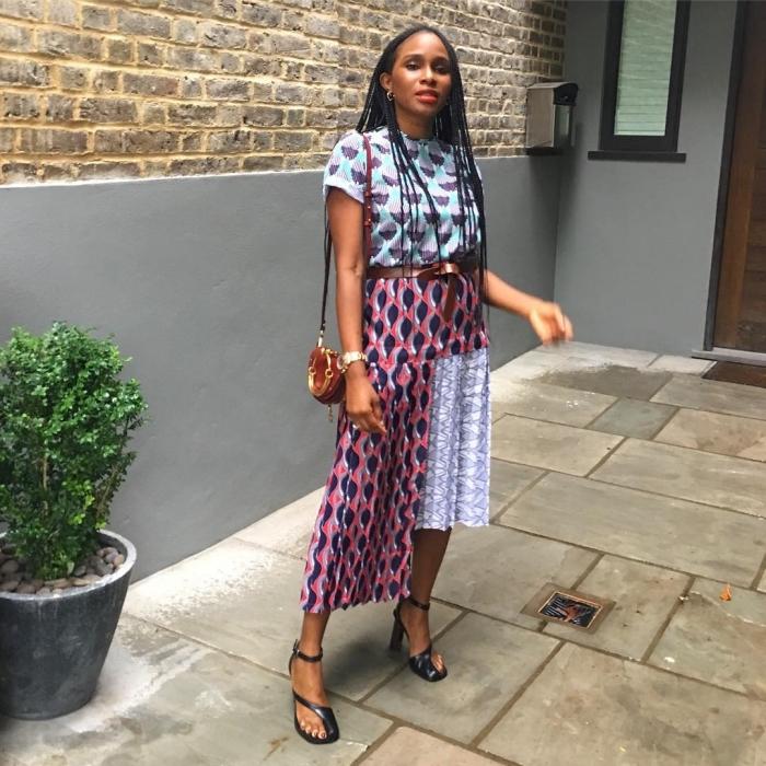 robe asymétrique qui joue sur divers motifs africains, portée avec une ceinture en cuir à la taille et des sandales à talons noir