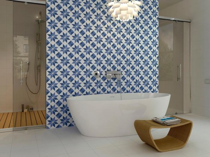 des carreaux de ciment salle de bain posés derrière la baignoire qui réveillent l'ambiance épurée avec leurs motifs marguerites bleues rétro