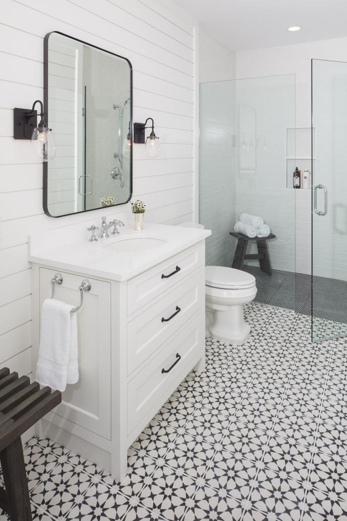 un modele de salle de bain al italienne qui joue sur les effet de matière avec son revêtement de sol en carreaux de ciment, son paroi de douche en verre et ses murs en lambris