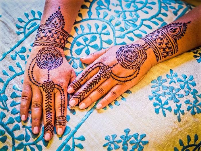 dessins symétriques au henné sur les mains et poignets de femme
