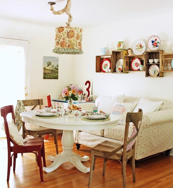 deco shabby chic dans la salle à manger en table blanche, chaises en bois, canapé fleuri, étagères en cagettes de bois, suspension shabby