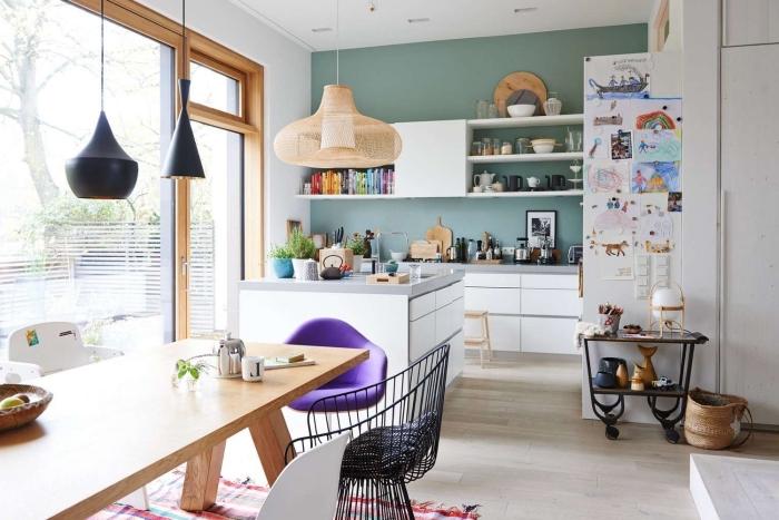 petite cuisine avec ilot central compact en blanc et gris qui sépare visuellement la cuisine et le séjour, un mur vert pour délimiter l'espace cuisine ouverte sur le salon