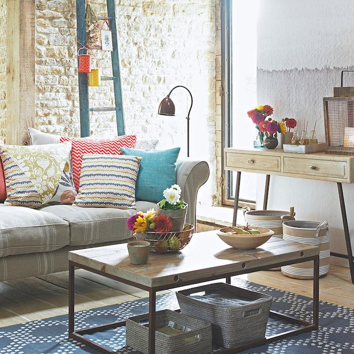 mur de briques blanches, canapé gris, coussins décoratifs colorés, tapis bleu, table basse bois et metal, console bois, echelle decorative, objets champetre, deco salon cosy