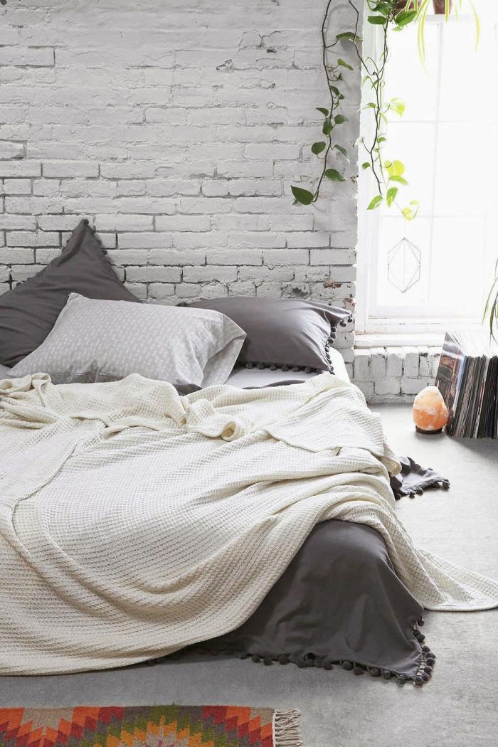 aménagement chambre scandinave, mur en briques blanches, bougeoir de sel, pot de fleur suspendu, lit gris et blanc