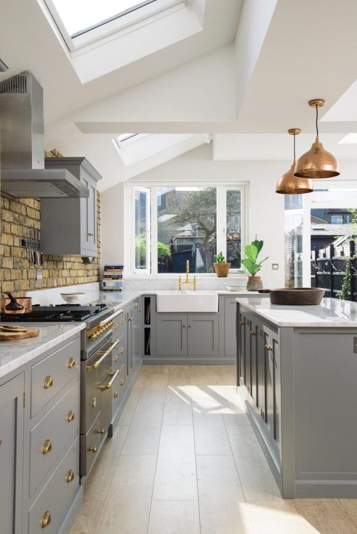 cuisine gris clair de style traditionnel aux accents industriels, aux armoires à finition mate avec des poignées dorées, cuisine ilot central qui fait partie intégrante du décor