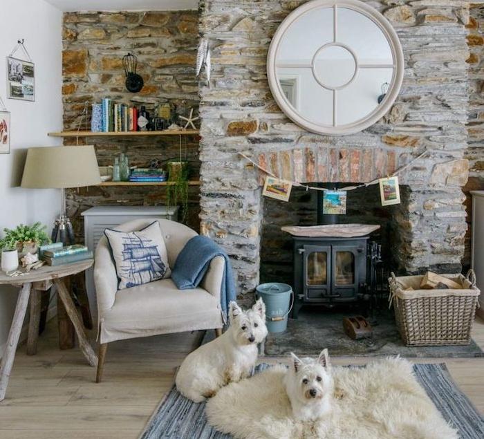 mur et cheminée en pierre, deco salon cosy cocooning, campagne anglaise, cheminée noire, grand miroir rond, fauteuil gris clair, étagères en bois, table d appoint bois brut